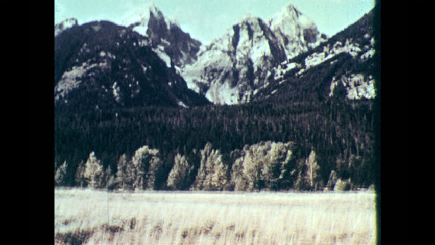 1960s: jagged mountain, dense evergreen trees  earthquake  diagram of  layers of earth, rock snaps at fault line  landslide, dust cloud rises