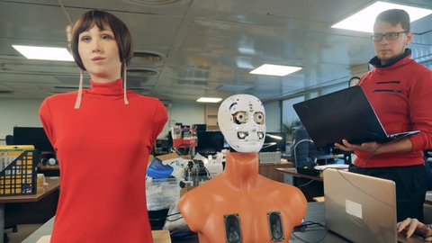 Robotic head and female mannequin are moving their mouths under expert's control