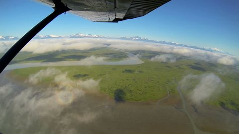 Aerial cloudscape wide angled view of large river melt waters swampland remote Alaskan Wilderness from light aircraft Northern Hemisphere, Alaska, USA