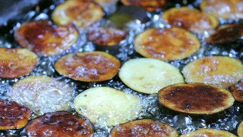 Vegetable fry in sunflower oil . Frying chopped eggplant in the pan . Sliced eggplant fried in a black frying pan . Professional chef mixing vegetables with a spatula . Oil splashes . Frying bubbles .