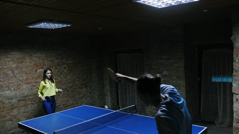 Young sporty girl playing table tennis with her friend. Ping-pong game