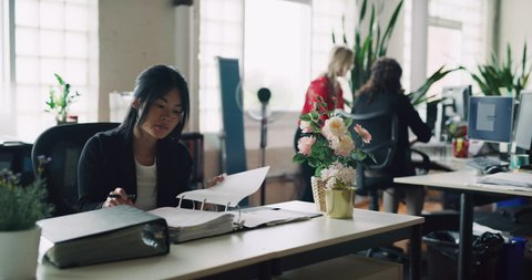 Busy bustling industrial modern architect office full of professional women in the daytime. Wide to medium shot on 4K RED camera on a gimbal tracking backwards.