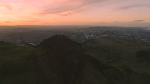 Flight around Arthur's Seat mountain, an extinct volcano, the main peak of the group of hills in Edinburgh, Scotland, which form most of Holyrood Park with Pentland hills and sunset sky on background.
