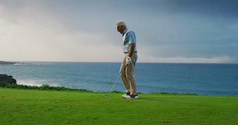 Handsome older golfer placing golf tee and taking practice swing, gorgeous oceanside golf