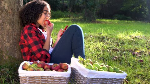 Beautiful African American mixed race teenage girl young woman sitting leaning against a tree in an orchard eating an apple using her mobile cell smart phone