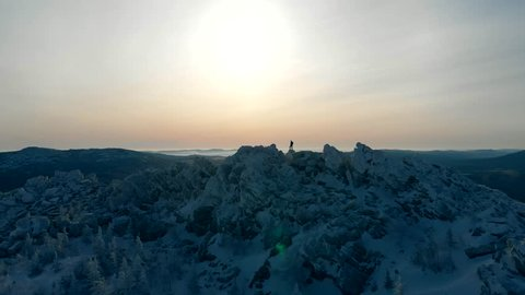 Aerial view over climber on top of the mountain, aerial. Tourist mountaineer silhouette on the summit. On the ridge - motivation and success concept. Hiking snow mountains, drone flight