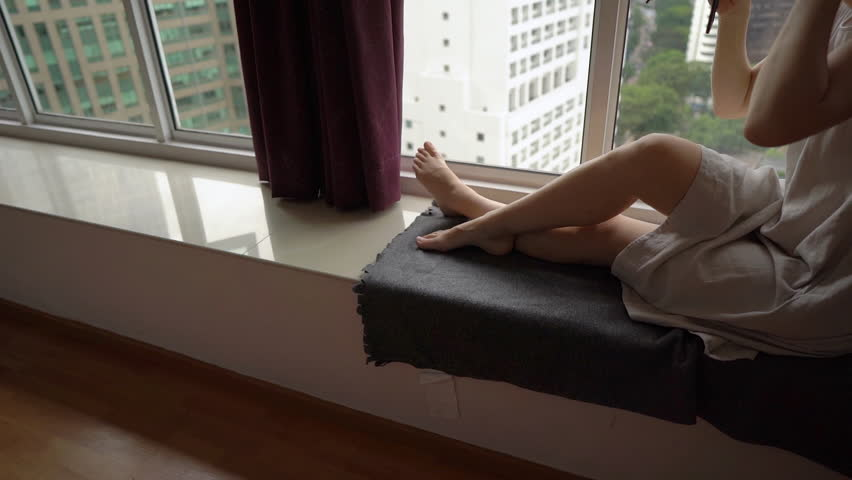 Super Slow Motion shot of a young woman doing her makeup sittng by a panoramic window in downtown of a city with skyscrapers at a background   Shutterstock HD Video #1023725767