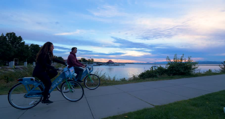Burlington, Vermont / United States - August 25 2018: Couple Biking Along Dock at Sunset, Boats in Water, Harbor #1023761287