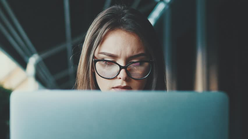 Young business lady sitting at a cafe working on a laptop. During this she is wearing glasses and is very serious. | Shutterstock HD Video #1023806857