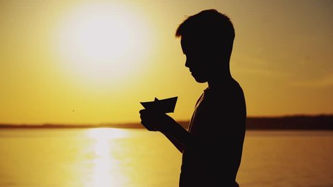 Young boy is making a paper ship standing near the river at the evening sunset. Silhouette of the boy playing with paper boat outside