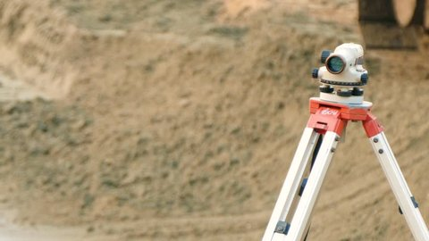 Theodolite on the background of the construction building, construction work. Tachymeter on the construction site. Surveyor engineering equipment.