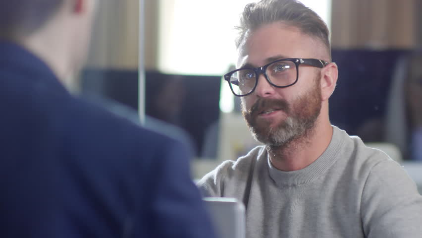 Close up shot of bearded young Caucasian man in glasses and casual clothes having conversation with unrecognizable male colleague seen from his back | Shutterstock HD Video #1023896857