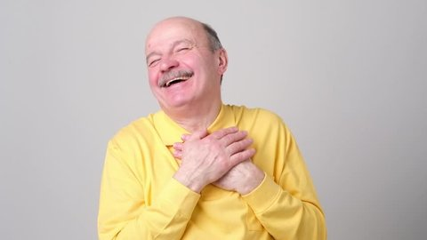Happy senior european man holding palms on heart and smiling thankful receiving compliments or gift