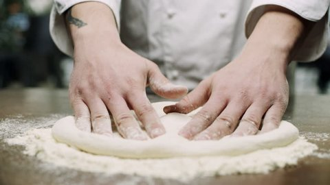 Italian pizza chef forming the dough on a floured surface and kneading it with his hands, in a traditional pizzeria kitchen. Close up shot on 8k helium RED camera.