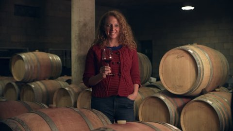 In a wine cellar, portrait of a woman woman holding a glass of red wine with barrels in the background. Medium shot on 8k helium RED camera.