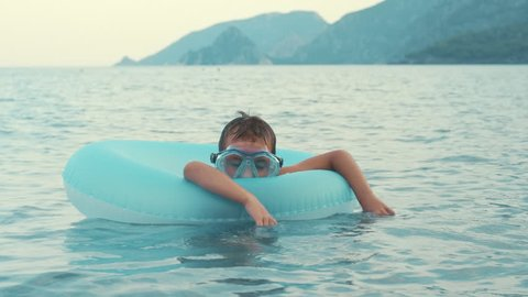 Little boy sleeping on rubber ring swimming in sea. Child relaxing on inflatable circle during summer holidays. Kid floating on inflatable circle in sea