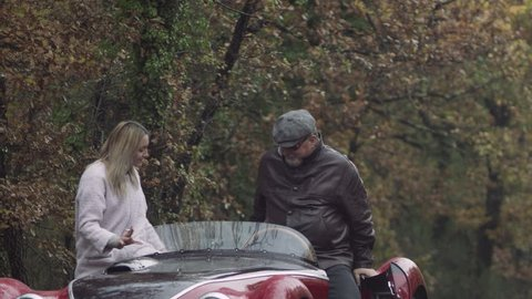 Older boyfriend and his younger girlfriend get into a vintage convertible sports car to continue driving, in Tuscany. Medium shot on 8k helium RED camera.