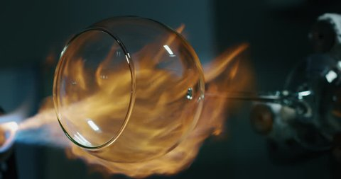 Slow motion macro of experienced glass blower working with flame on a handmade wine glass from crystal in a workshop. Shot in 8K. Concept of handmade, high quality, artisan, made in Italy,glass blower