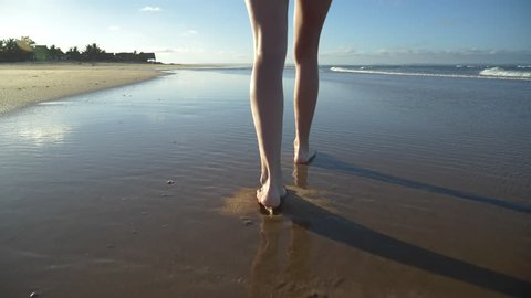 4K slow motion cropped rear view of a young woman's legs walking along the waters edge on the beach, South Africa