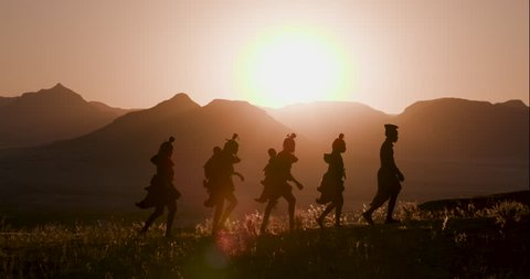 4K view of people from the Himba tribe in traditional dress, walking along a path with scenic mountains in the background, Namib desert, Namibia