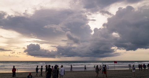 Bali, Indonesia: February 3rd 2019: Timelapse of clouds rolling over Seminyak Beach with visitors taking pictures