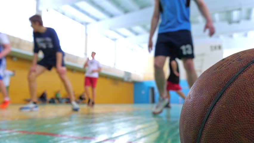 Basketball game. Teens train in the school old sports hall, throw the ball in the basket and run with the ball. | Shutterstock HD Video #1024080467