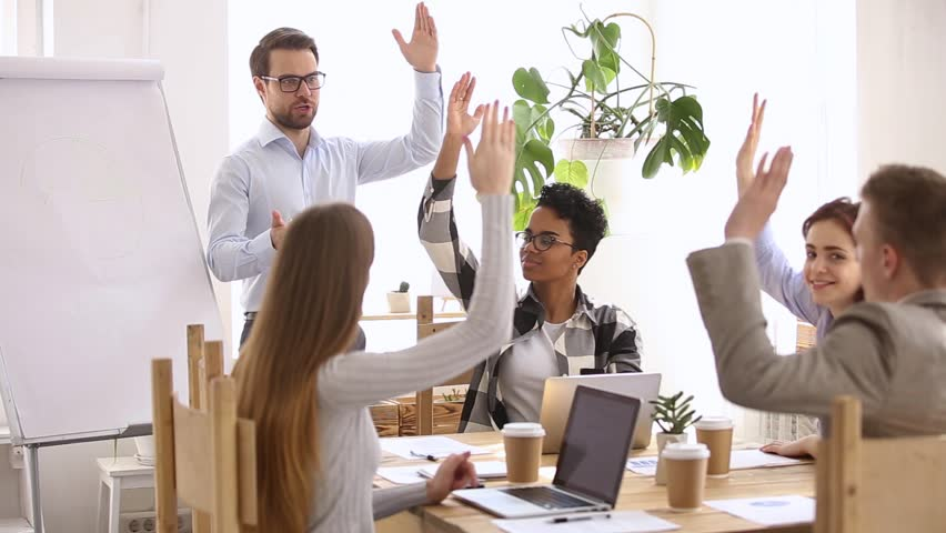 Multi-ethnic business team and leader speaker raising hands engaged in voting volunteering at group meeting, participating in teambuilding activity at corporate conference training with coach mentor | Shutterstock HD Video #1024093877