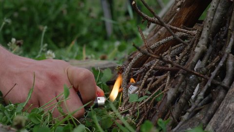 SLOW MOTION, MACRO, DOF: Man's hand holds a lighter and ignites a campfire set up in the wilderness. Unrecognizable man lights up a campfire during a camping trip. Traveler igniting paper and kindling