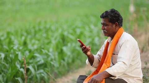 Indian farmer using mobile phone at field