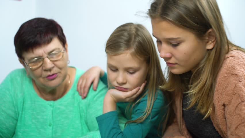 girls watching old photo album with their grandmother #1024138817