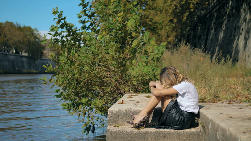 Desperation,loneliness,sadness. Lonely sad fashion woman crouched near the river | Shutterstock HD Video #1024147607