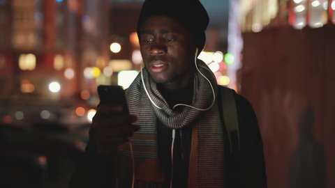 Closeup of african american man listening to music from smartphone in earphones walking at night city, slowmotion