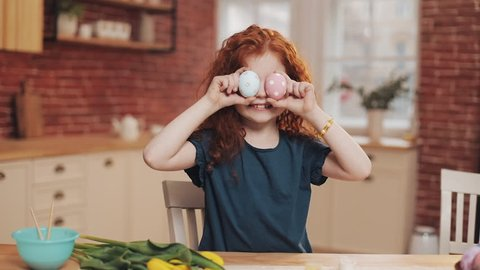 Portrait of cheerful redhead little kid girl playing with easter egg on the kitchen background. She is cheering and having fun at the camera. Happy Easter