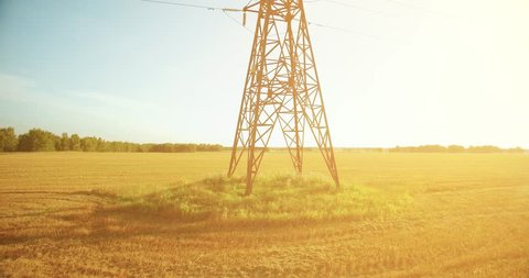UHD 4K aerial view. Vertical movement flight near high voltage electricity tower and power lines at green and yellow wheat rural field at sunny summer day. Sun rays on horizon.