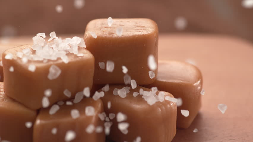 Salt falling onto caramel pieces in slow motion.  Shot with Phantom Flex 4K camera. | Shutterstock HD Video #1024261457