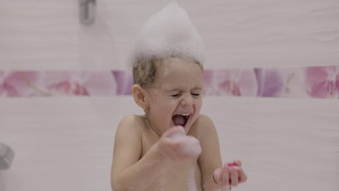 Attractive three years old girl  takes a bath. Wet hair with bath foam.  Cute blonde child. Brown eyes. Cute girl smiling. Pretty little child, 3-4 year old blonde girl in bathroom