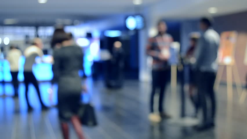 Blurred Background. People are standing behind counter in of white hall. People in black business suit standing in space and communication. Crowd lot of people. Gray blueblurred Abstract Background | Shutterstock HD Video #1024297817