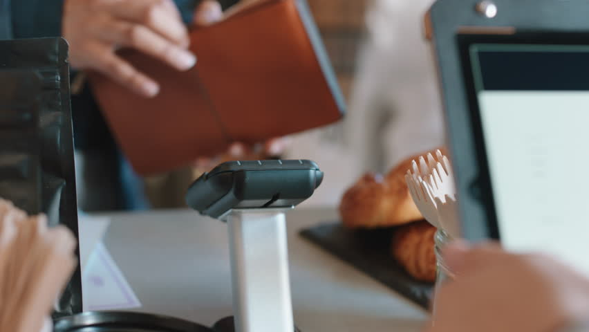 Close up customer paying using credit card contactless payment spending money in cafe with digital transaction service | Shutterstock HD Video #1024313237