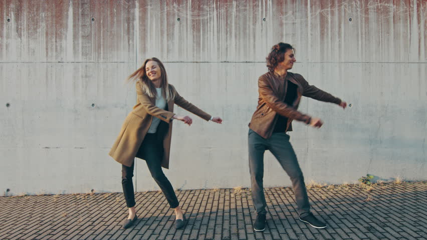 Cheerful Girl and Happy Young Man with Long Hair are Actively Dancing Meme Moves on a Street next to an Urban Concrete Wall. They Wear Brown Leather Jacket and Coat. Sunny Day.