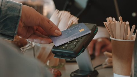 close up customer paying using credit card contactless payment spending money in cafe with digital transaction service