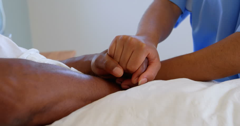 Close-up of female doctor holding mature man hand in a comfortable home. Mid section of doctor consoling man 4k | Shutterstock HD Video #1024371407