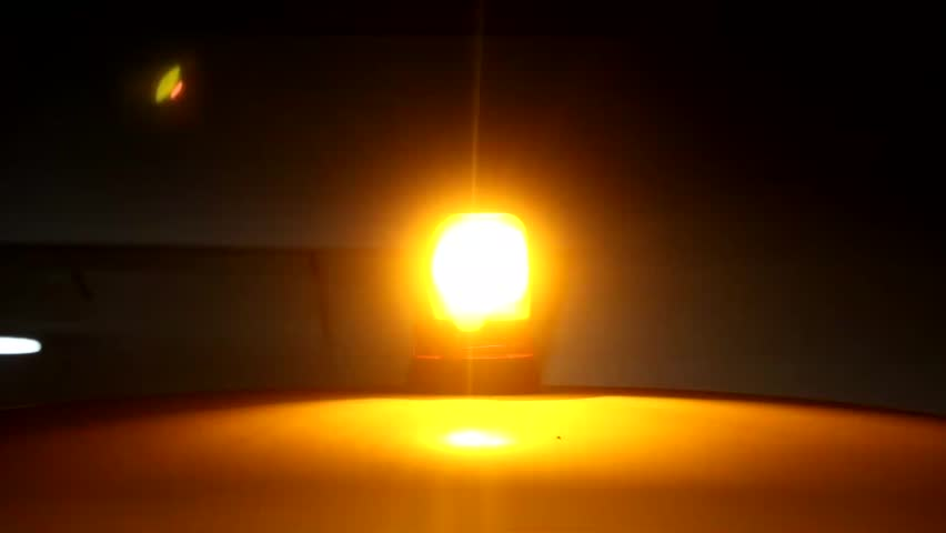 Orange beacon to change direction of rotation when working. Emergency Light flashing in night. Orange flashing and revolving light on top of a support and services vehicle.