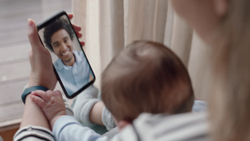 Mother and baby having video chat with father using smartphone waving at infant enjoying communicating with family on mobile phone connection