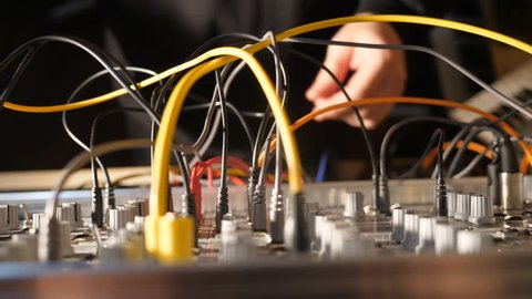 Electronic musician works on a live mix. Modular synthesizer with cables. Handheld shot with stabilized camera. Shallow depth of field with focus on cables and knobs.