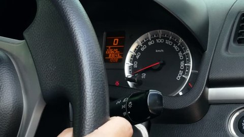 Close up of Asian woman hand use the signal switch Turn to right in modern car. Using the car safely on the road concept.