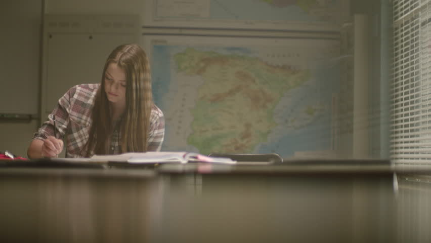 Female student in classroom surrounded by textbooks writes in her notebook working on school work in a classroom setting with map behind her. Filmed with Arri Alexa Mini