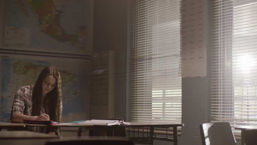 Young female student in class, writes in her notebook working on school work in a classroom setting. Filmed with Arri Alexa Mini | Shutterstock HD Video #1024494827