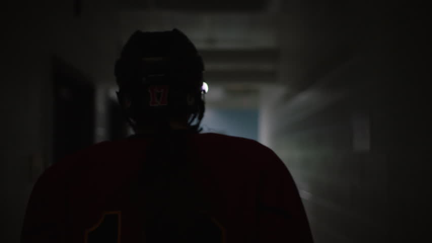 Dramatic silhouette of ice hockey player walking from changeroom in slow motion towards arena. Filmed with Arri Alexa Mini