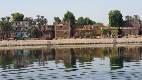 Sailing on river Nile in Egypt at Edfu through rural countryside landscape with african houses on riverbank