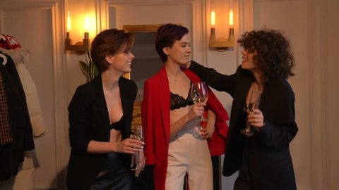Two women dressed in black jackets and a woman dressed in a red jacket stand side by side, in the hands of nah glasses with drinks, they talk, pose, smile and daredevil6 talk and discuss something